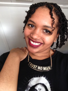 Smiling Cassandra in red lipstick with her hand on her shoulder wearing a necklace that reads Trust No Man.