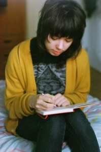 Photo of a dark-haired zinester wearing a yellow cardigan and writing in a notebook.