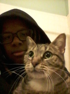 Joyce wearing a black hoodie and glasses posing with a cat (that has a freaked out expression).