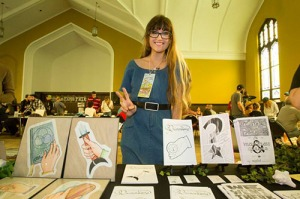 Maggie Negrete, a long blond-haired person, standing behind a row of their zines at a zine fest.