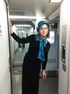 A person leaning on the wall of a train car wearing a long black dress with blue hat and scarf (great accessorizing!)