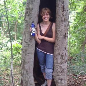 Anna smiling with a water bottle from inside a cleaved tree.