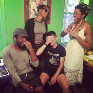 A laughing crew of zinesters making fun expressions in a room with bright green walls.