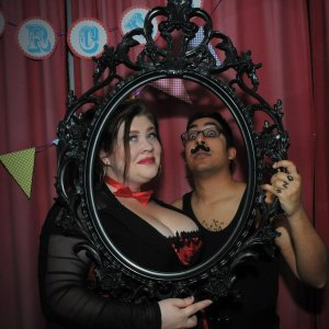 Two of The Wheelhouse zinesters, Lauren and Aus, posing behind an empty ornate black frame.